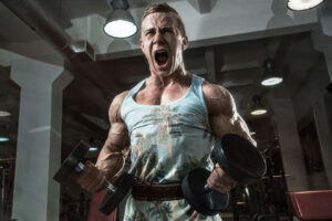 Man shouting during dumbbell curl exercise