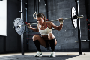 Woman doing barbell squat in crossfit gym