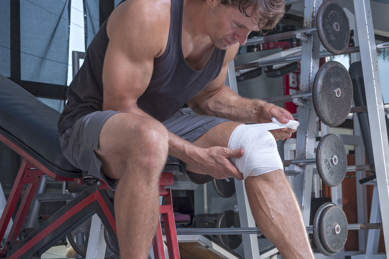 Man wrapping knee after gym accident