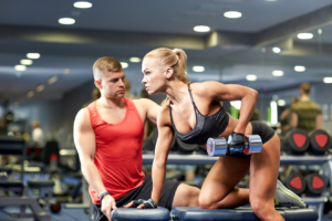Personal trainer helping woman to do dumbbell row exercise