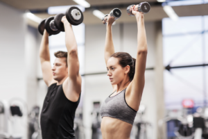 Man and woman doing dumbbell overhead press