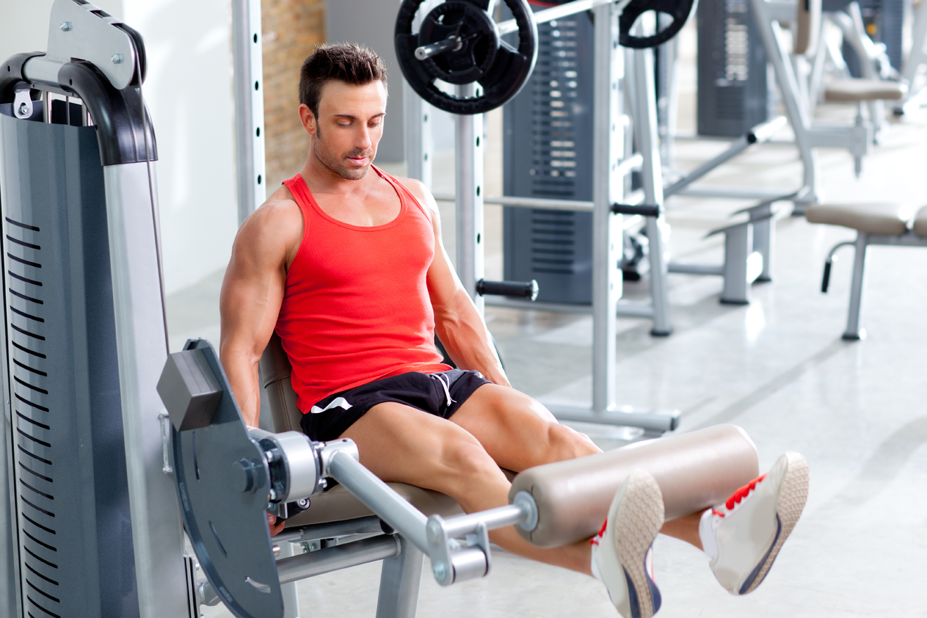 Man doing leg extension exercise in gym