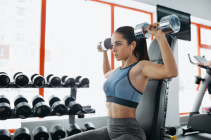 Woman in gym doing dumbbell shoulder press