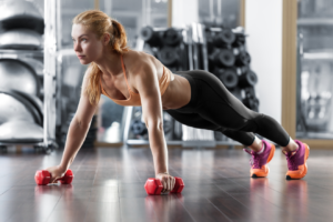Woman doing push-ups with dumbbells in hands