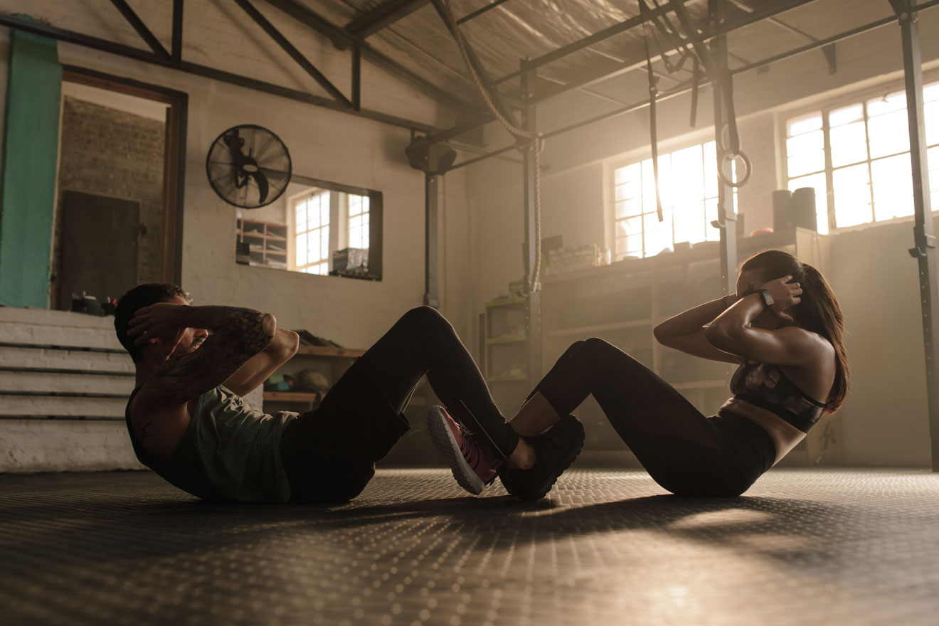 Man and woman locking legs and doing situps