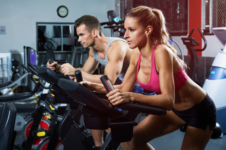 Man and woman on exercises bikes