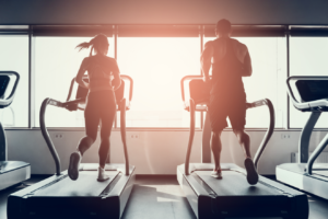 Man and woman running on treadmill